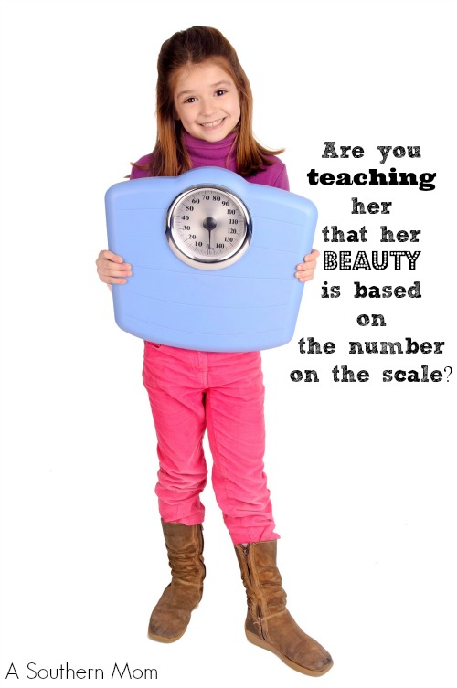 little girl holding a scale